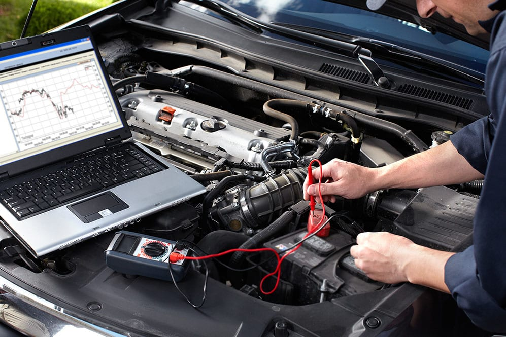 mechanic with laptop checking engine